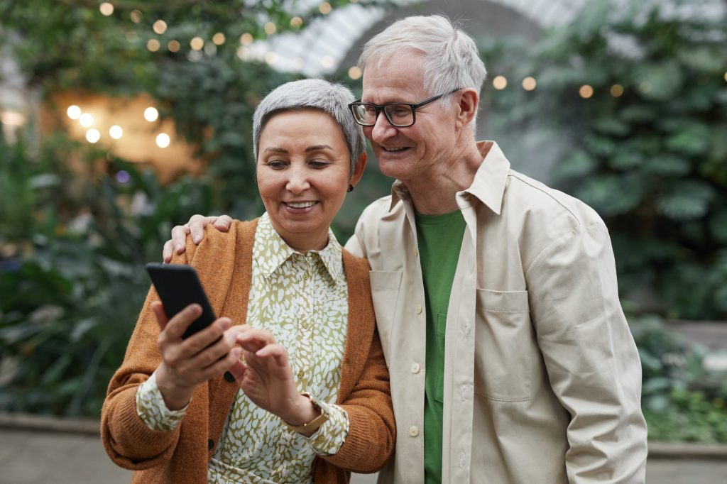 couple smiling while looking at a smartphone